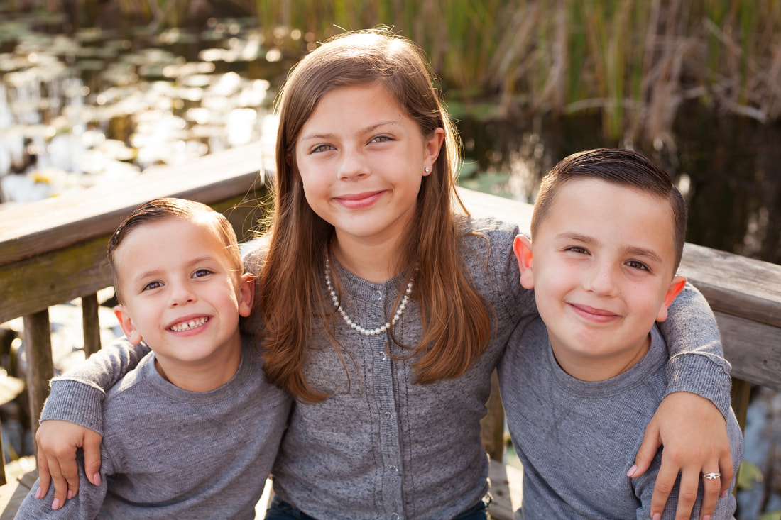 Portrait of three siblings on dock in new port richey