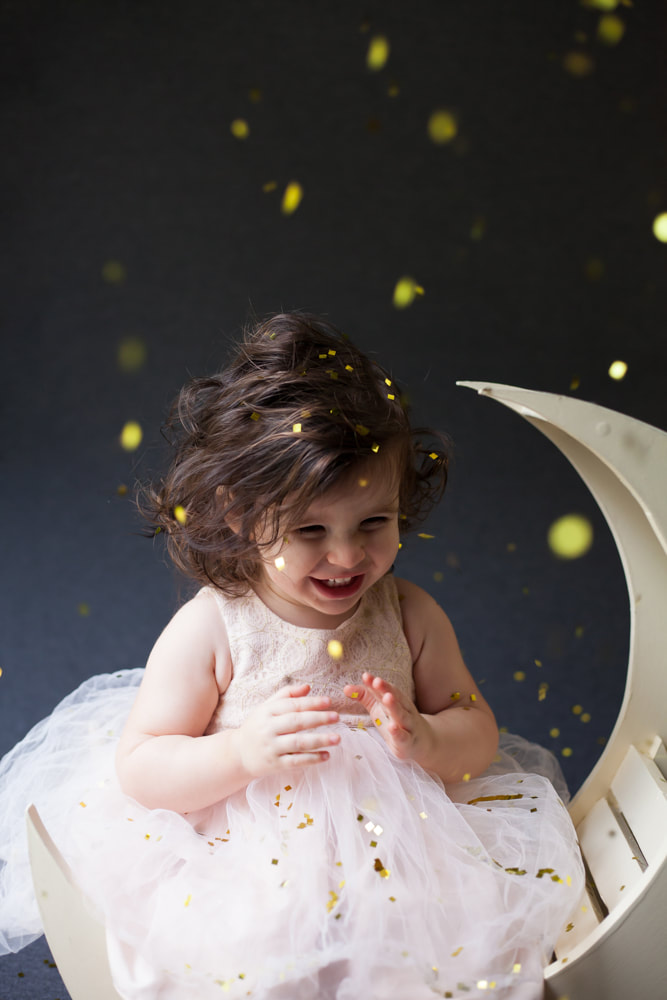Baby laughs and smiles as confetti falls on her