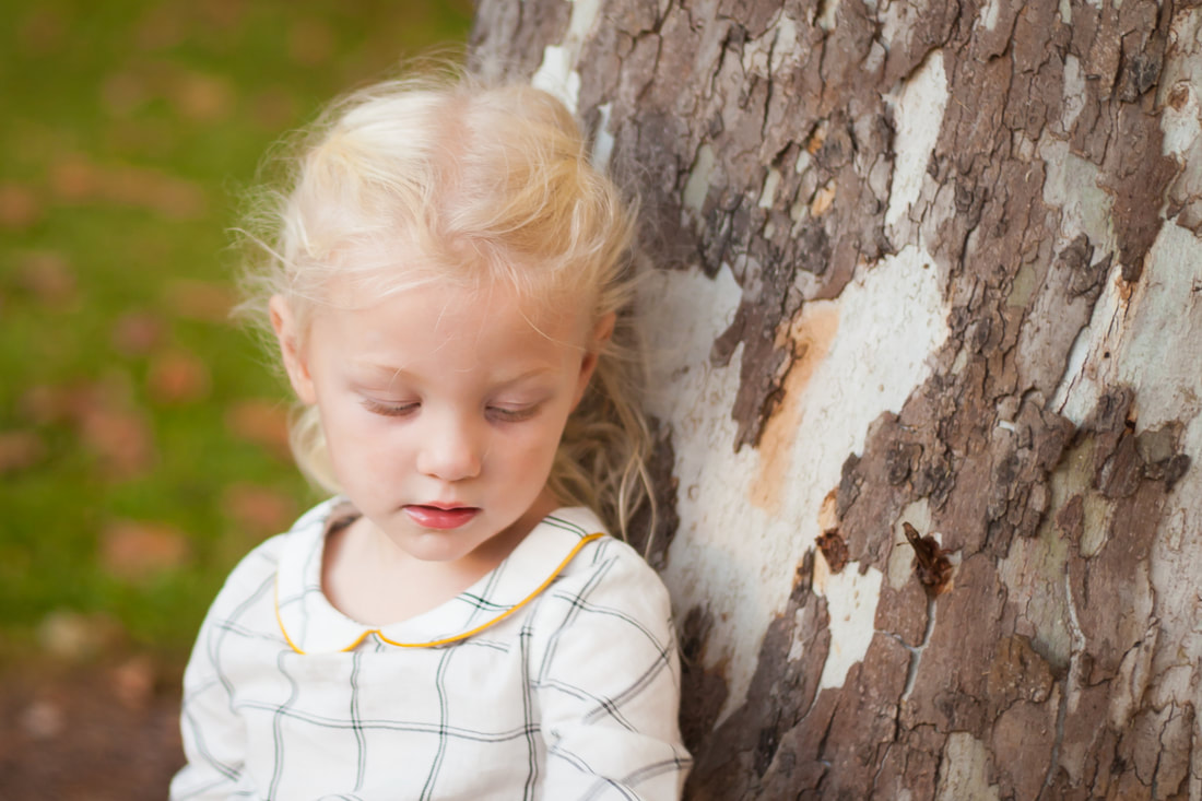 Little girl looks down sweetly while reclining against a tree