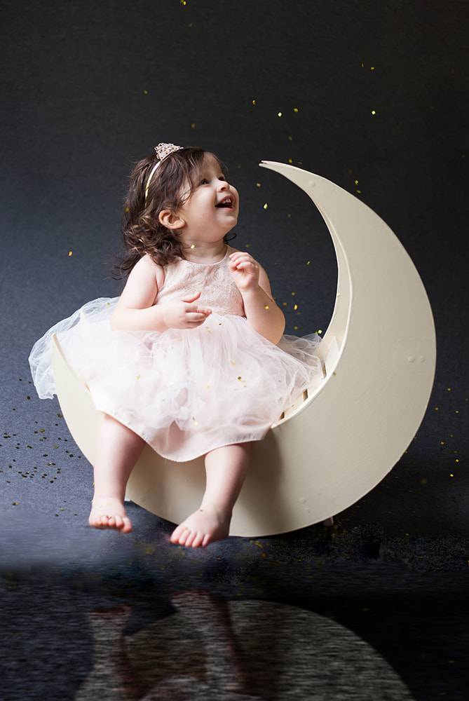 toddler sits on a moon with her reflection below her