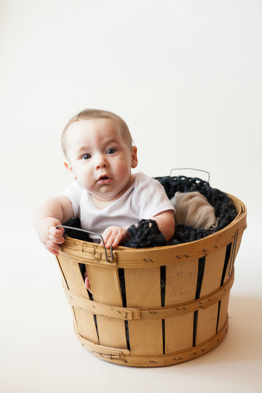 Baby boy in basket looks into camera in Wesley Chapel FL