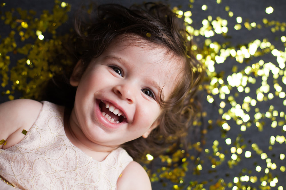 Baby girl looks up laughing with a smile in a studio in Tampa
