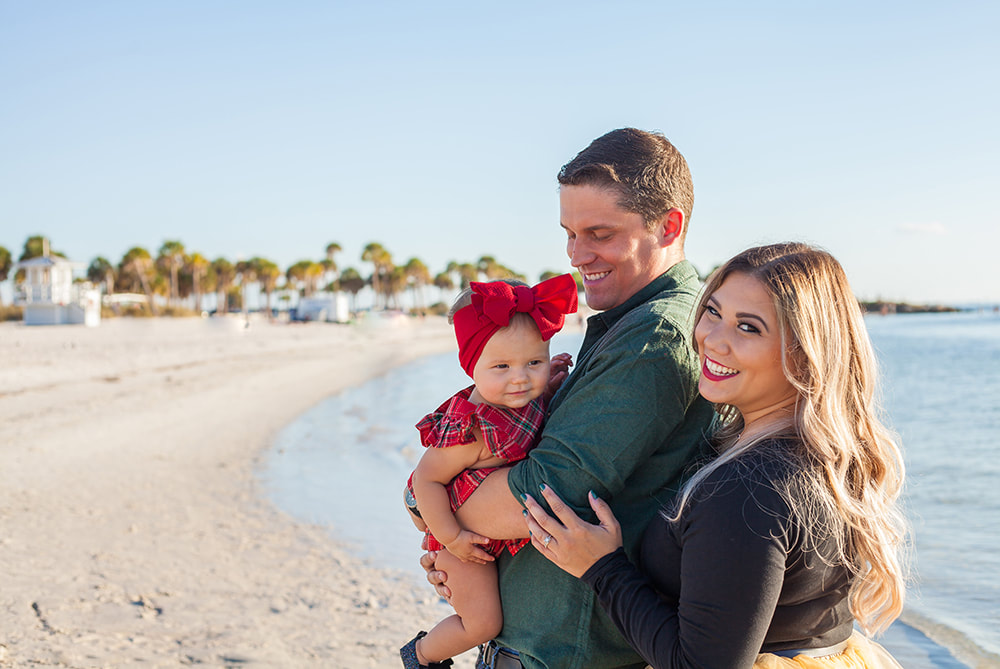 Family of three smiling on the beach in Tarpon Springs, FL