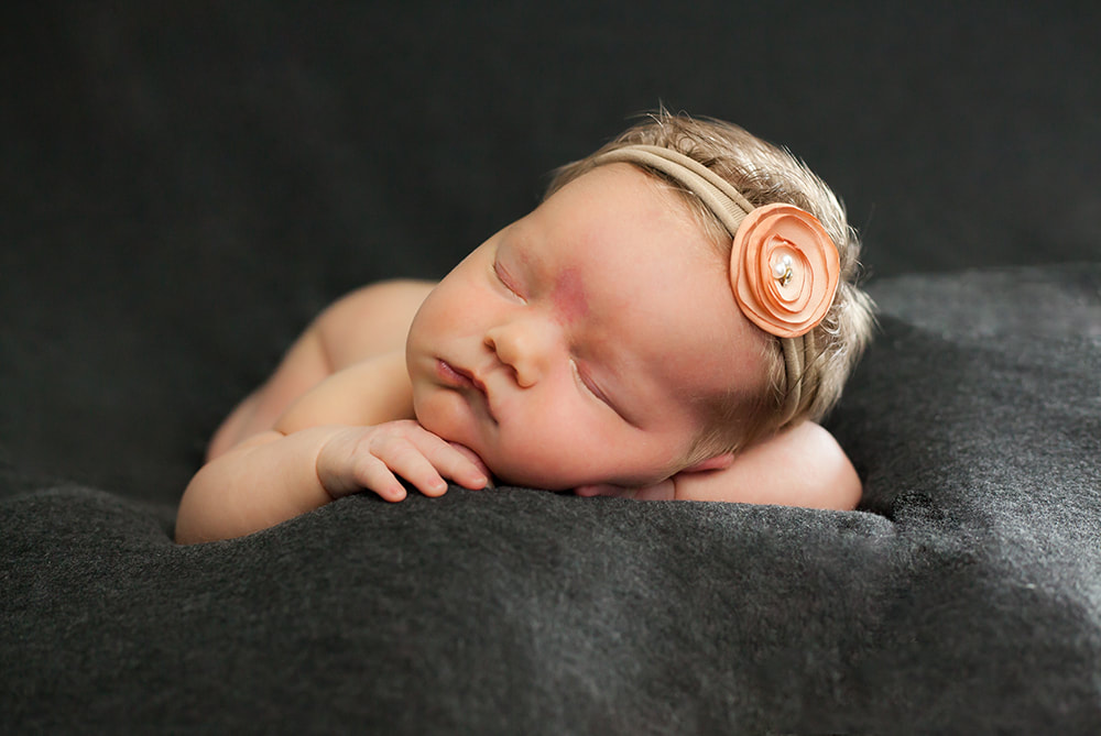 newborn baby girl lying on tummy on a dark gray background