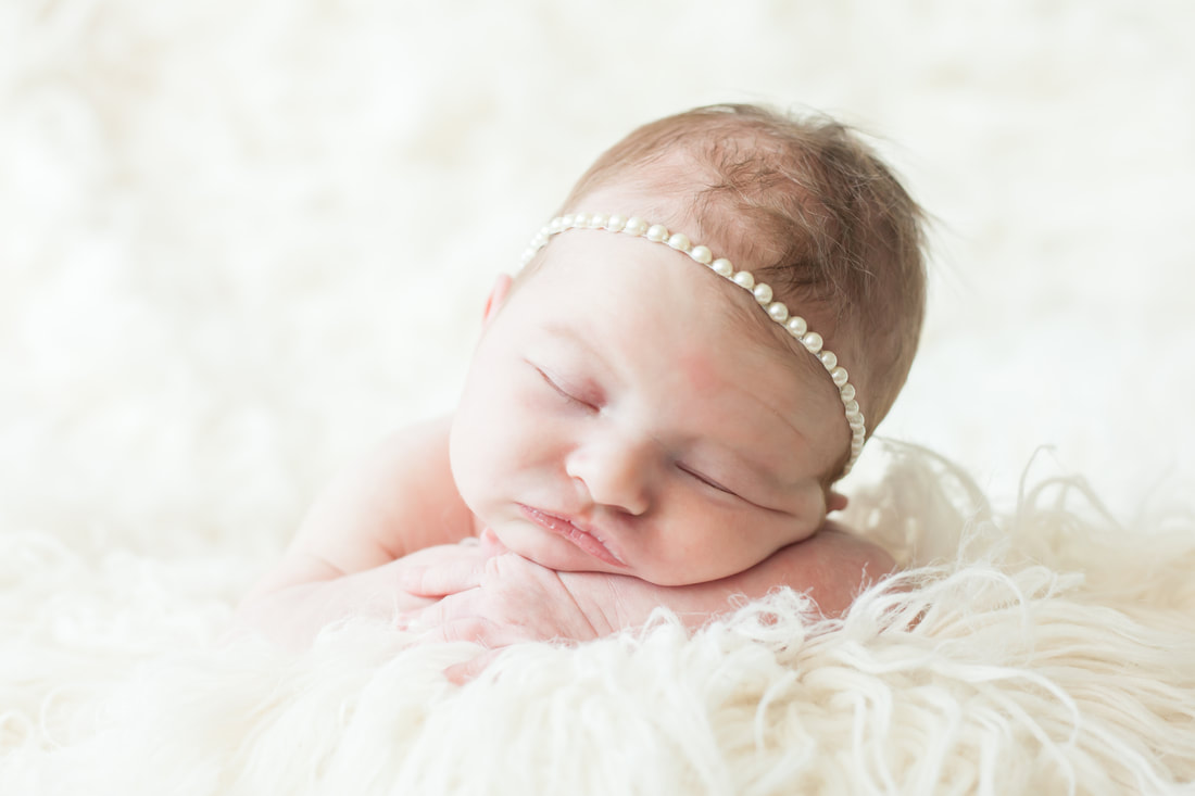 baby wearing a pearl headband sleeps on a cloud of white fur