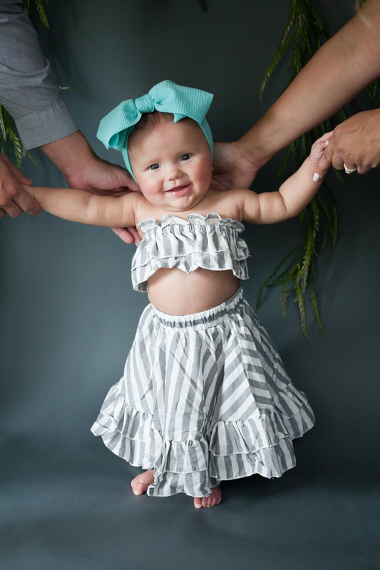 Smiling baby girl standing and holding onto her parents hands wearing gray and white striped two piece outfit
