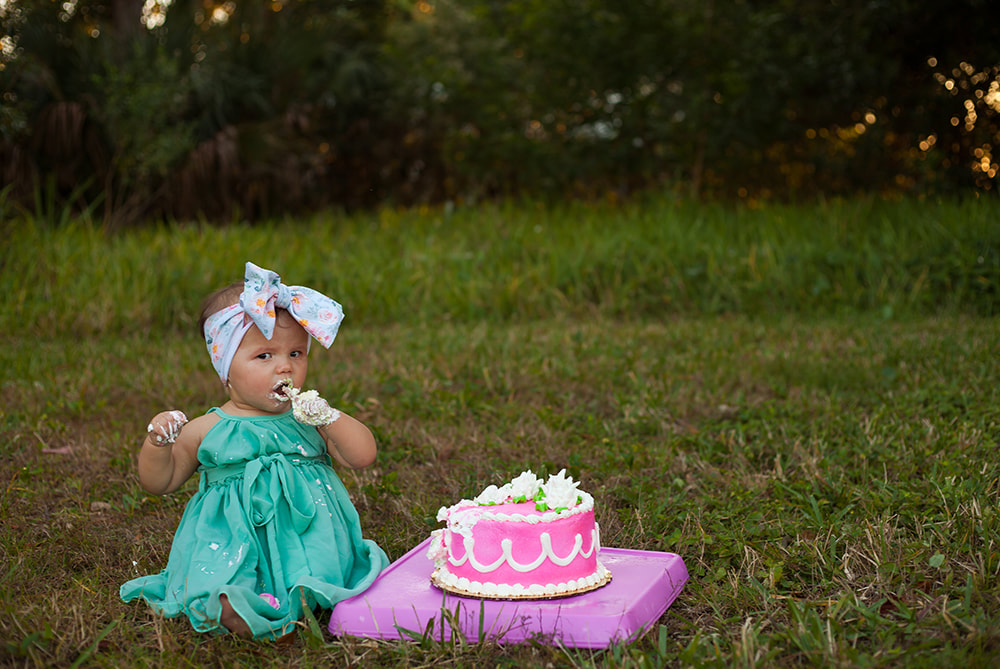 One year old baby girl enjoys her cake with pink frosting