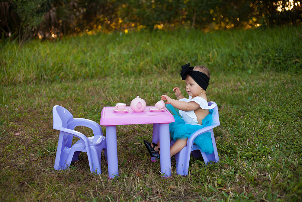 One year old baby girl having a tea party in a dreamy field