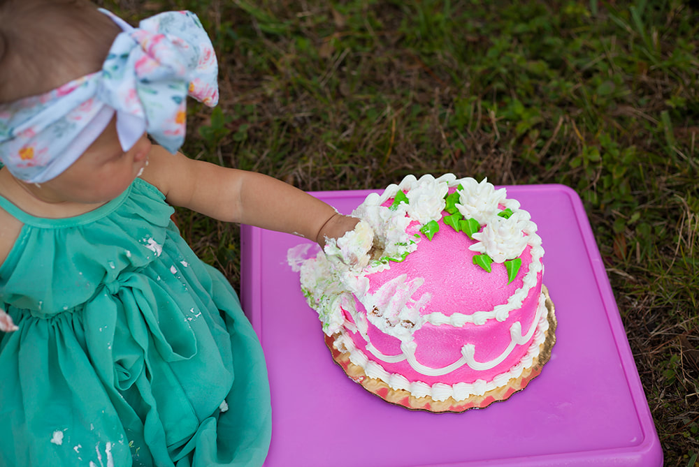 Close up of baby's hand smooshing into cake