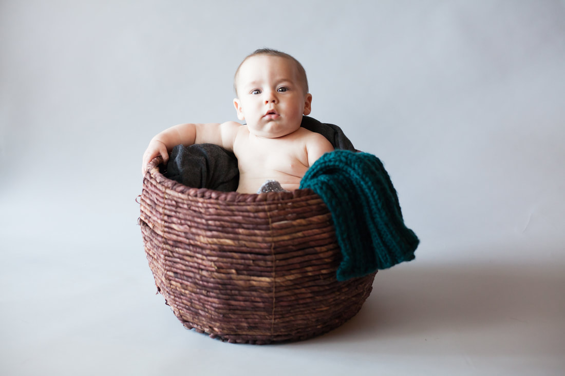 Chunky Baby sits in brown basket on Grey background