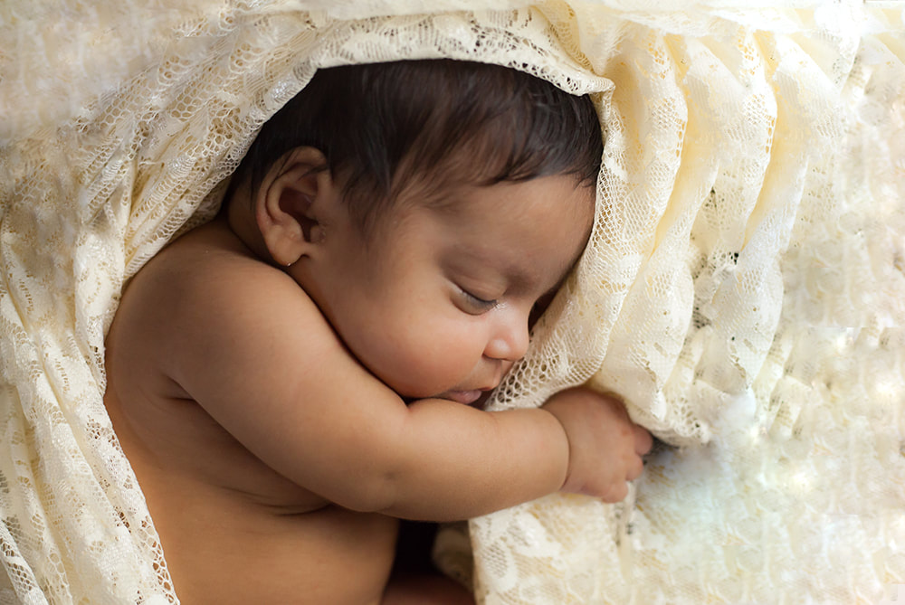 newborn baby sleeping surrounded by lace