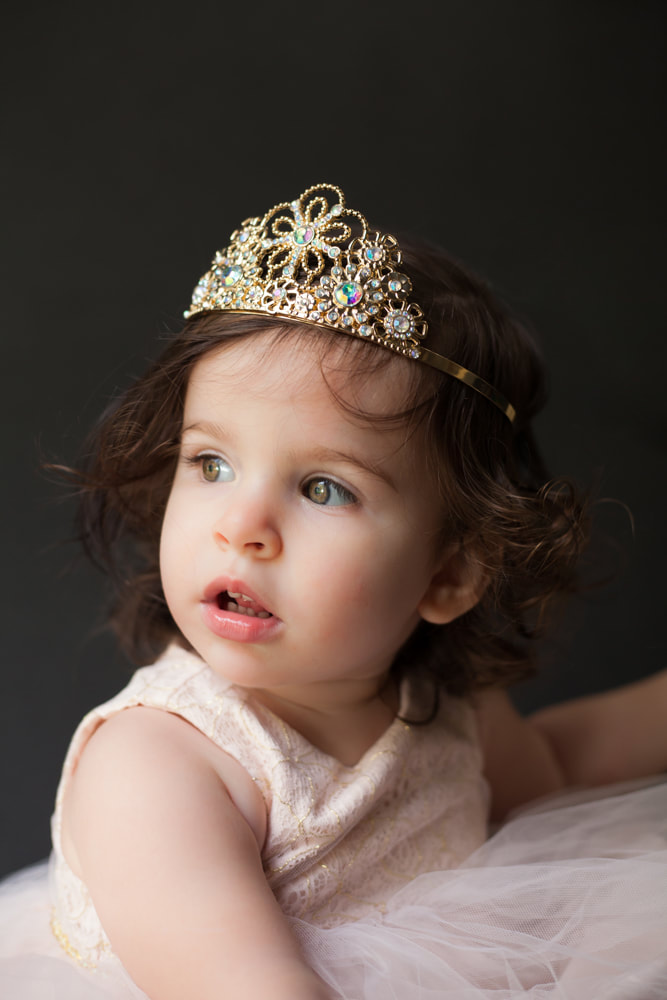 Sweet toddler wearing a tiara looks up off camera