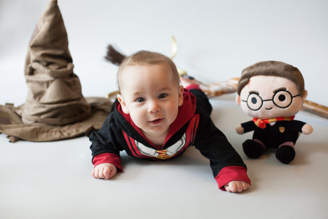 Baby in harry potter costume lying on stomach with harry potter props.