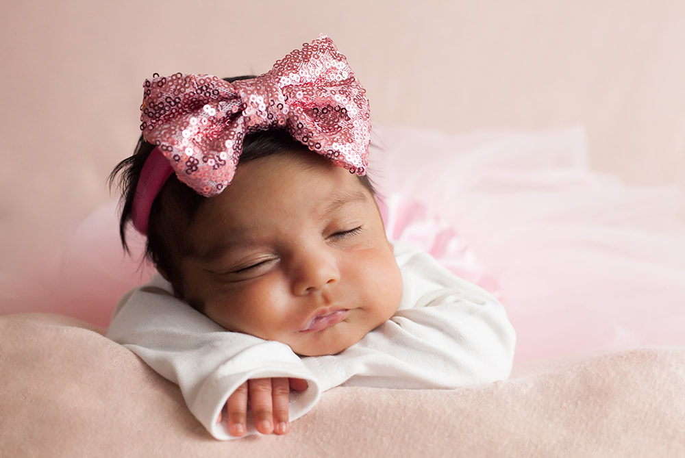 newborn baby girl in a tutu and sparkly headband lying on her tummy in Tampa, Fl