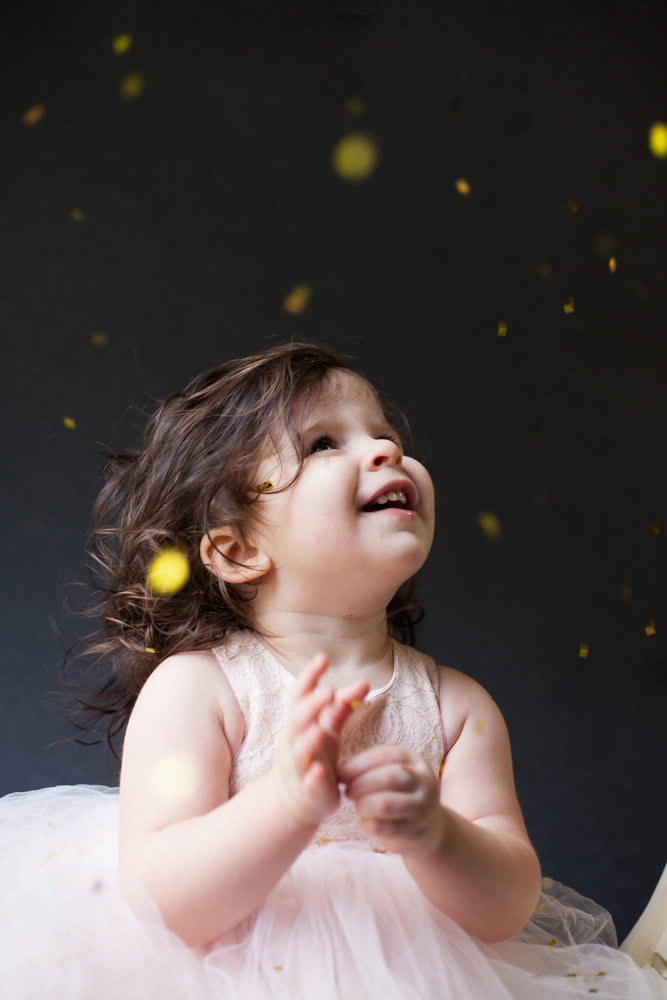 18 month old baby looks up and glitter and confetti falling on her