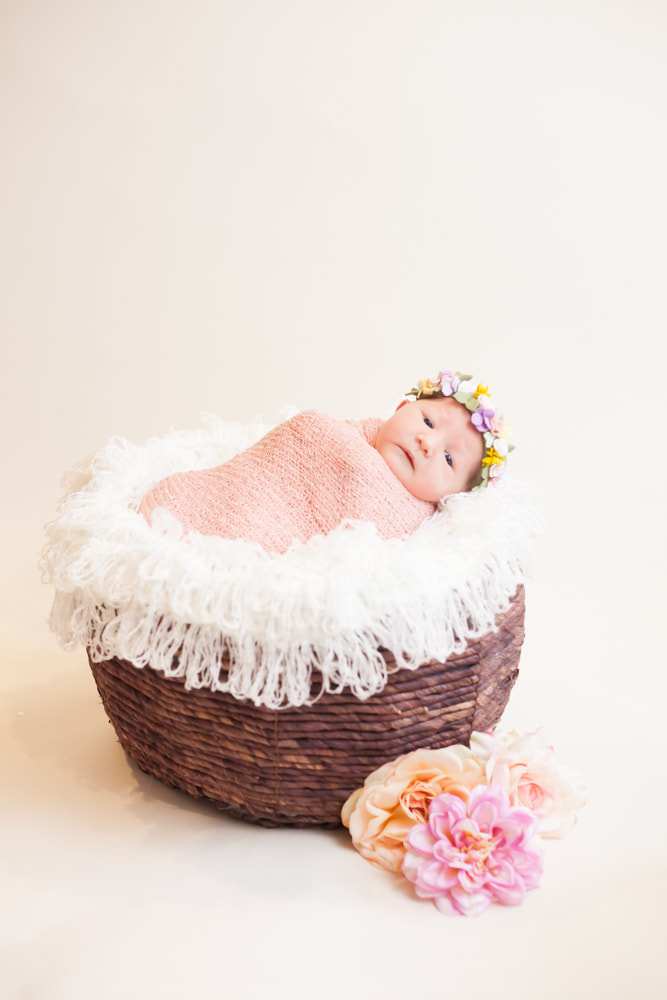 In home photograph of newborn baby swaddled and lying in a brown basket