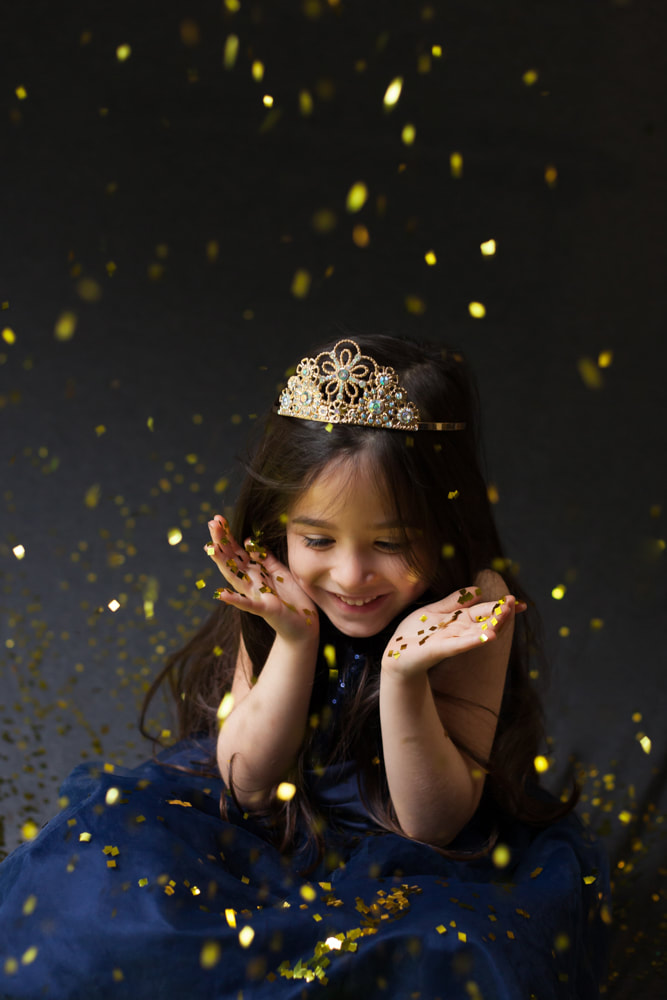 Five year old smiles as confetti falls around her in a photo studio in Tampa