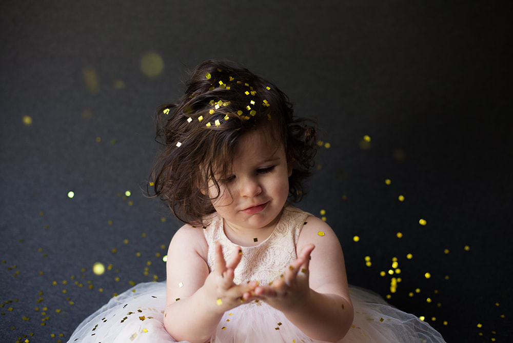 Baby girl looks at her confetti covered hands quizzically