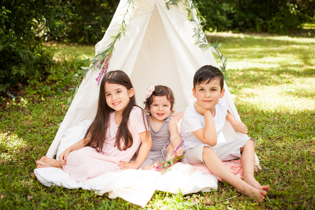 Three young children in light colors smile sitting in front of the opening of a white tent