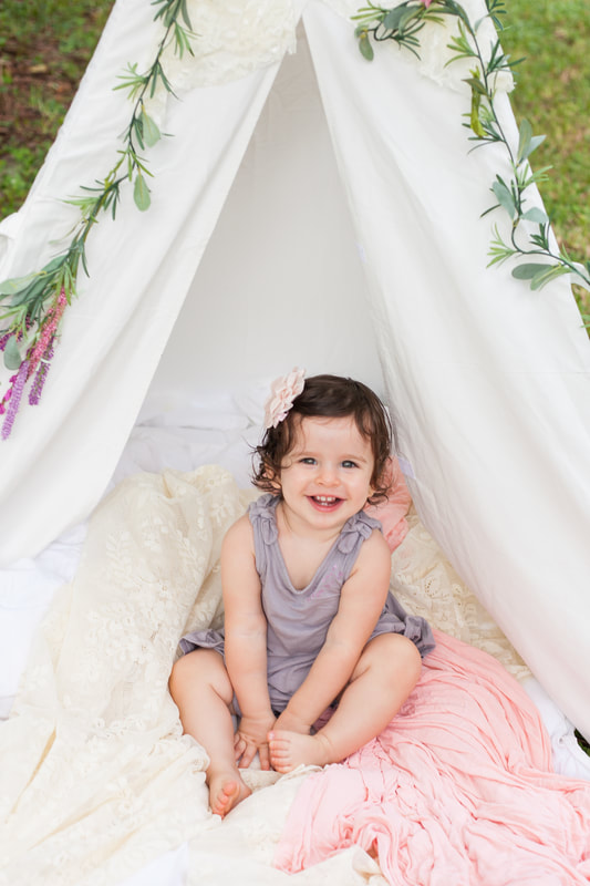 Baby girl smiles up at camera while sitting in a white tent