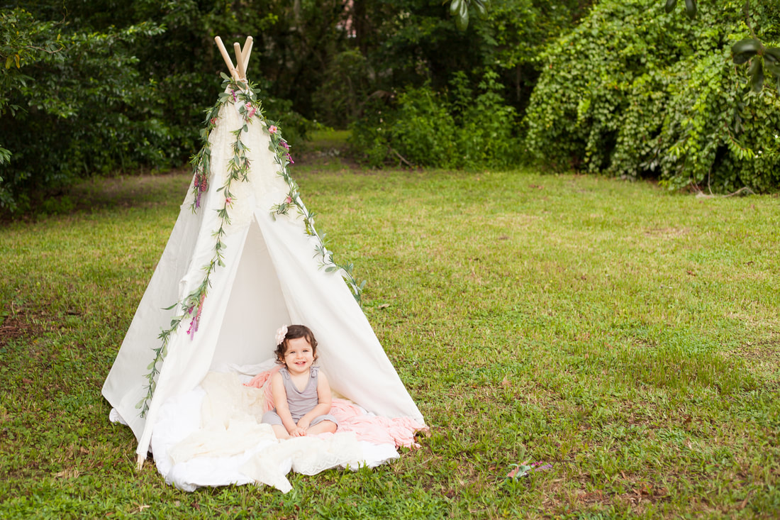 Baby sits in front of white tent in a beautiful field in Odessa FL