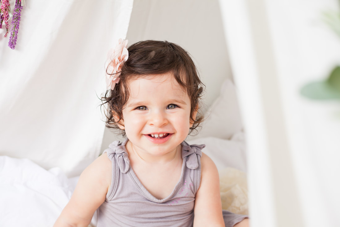 Smiling One year old baby in front of a bright gauzy background in Tampa FL