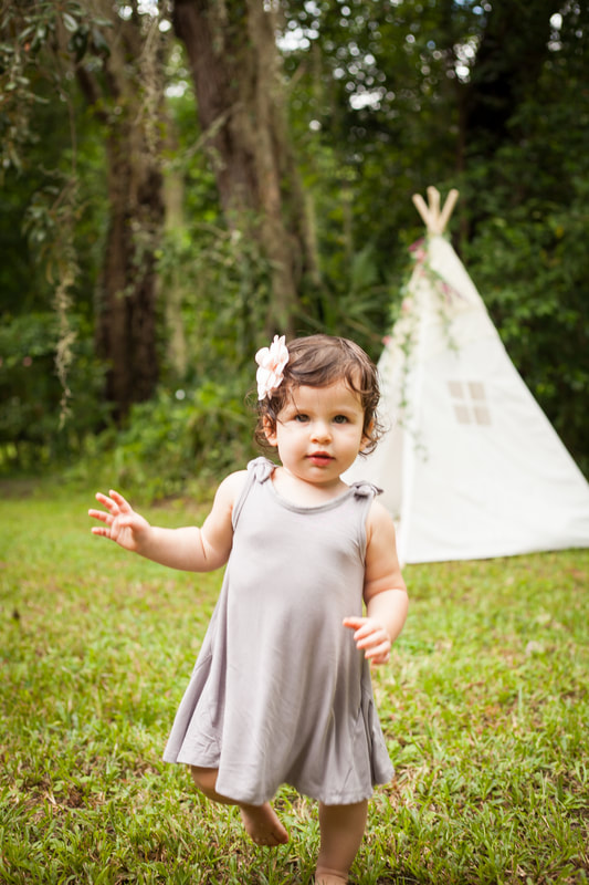 Cute one year old baby walks towards camera with a white tent and greenery behind her