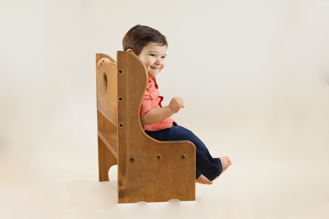 Smiling one year old sitting on wooden bench