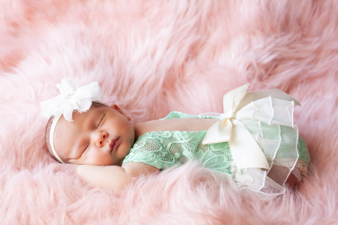 Newborn baby girl in teal lace sleeping on her stomach in a cloud of pink fur