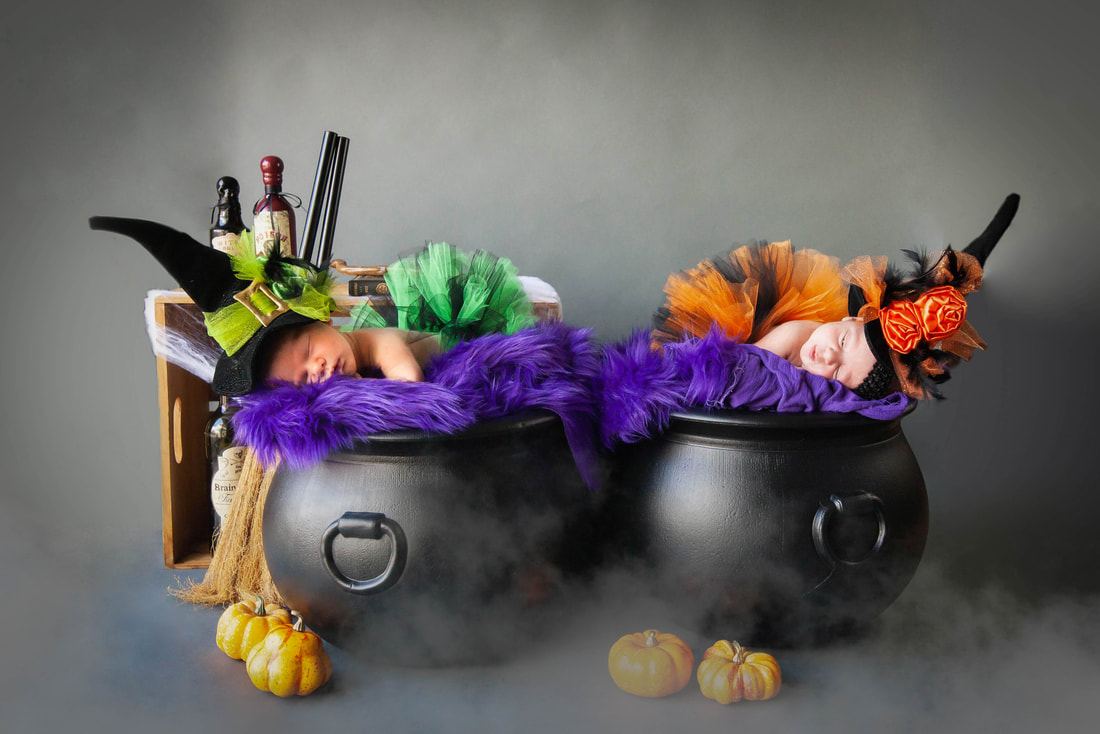 Newborn baby girls in witch hats laying inside cauldrons.