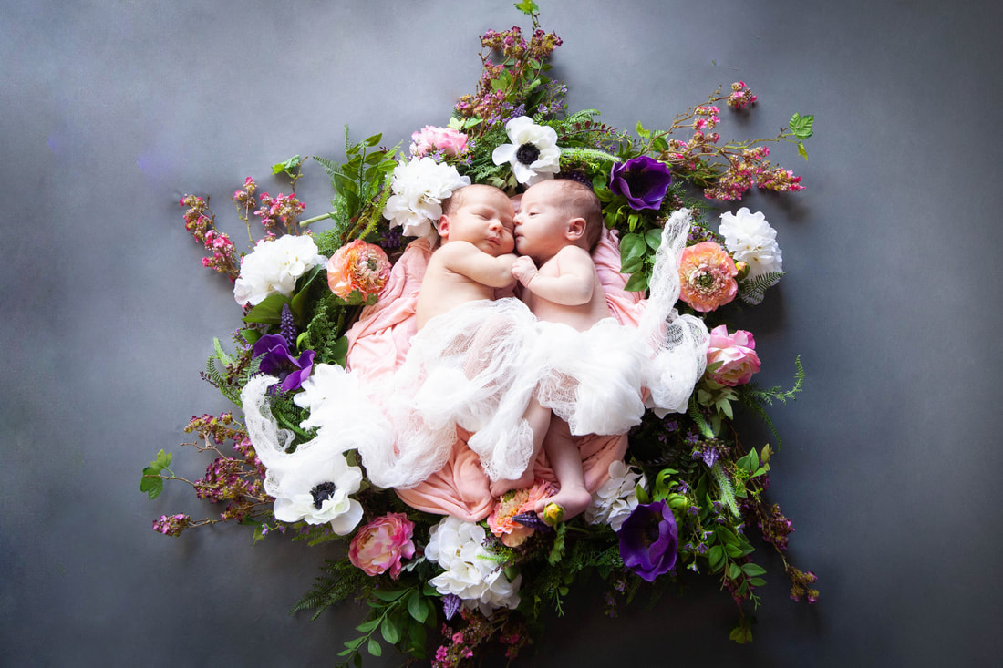 Twin baby girls snuggled close inside a ring of multicolored flowers