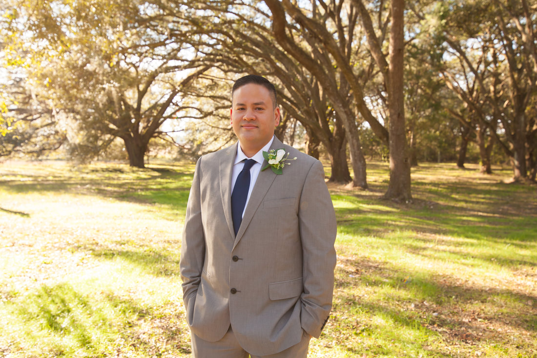 Groom smiles in front of arching trees