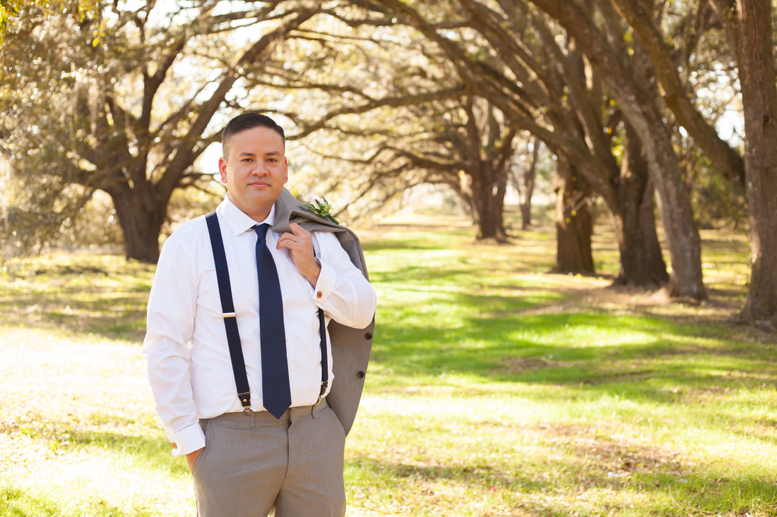 Groom stands with jacket over shoulder