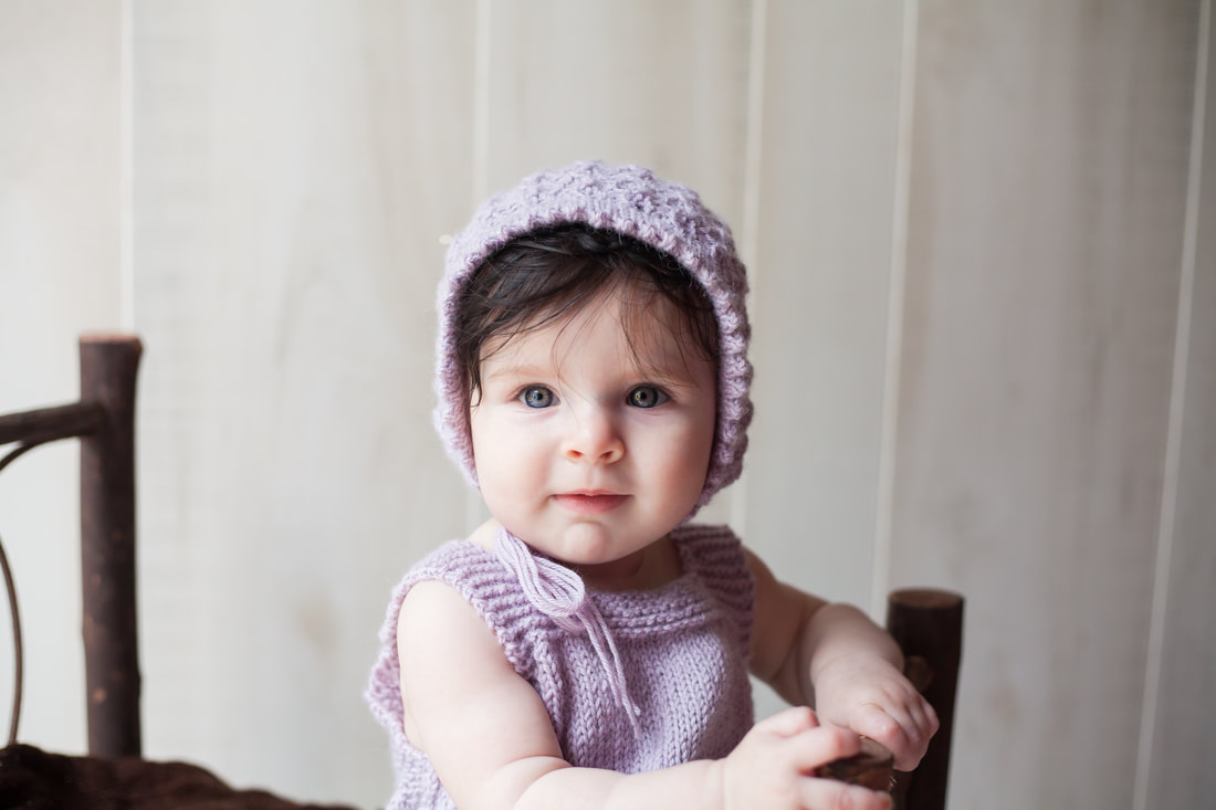 Serious six month old girl with bonnet