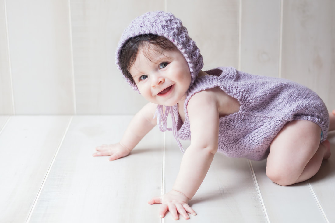 Smiling baby girl in purple crawling