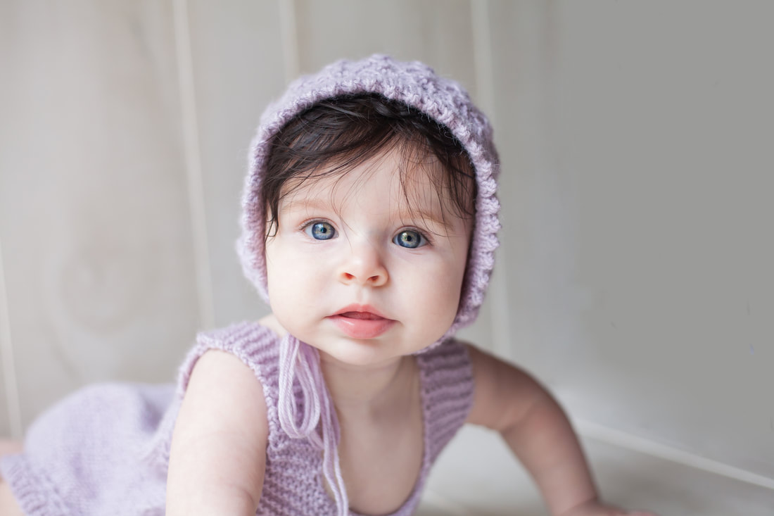 Close up portrait of baby with purple bonnet on