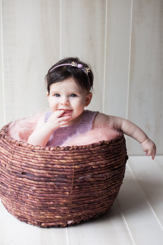 Smiling baby sits in basket at her six month milestone shoot