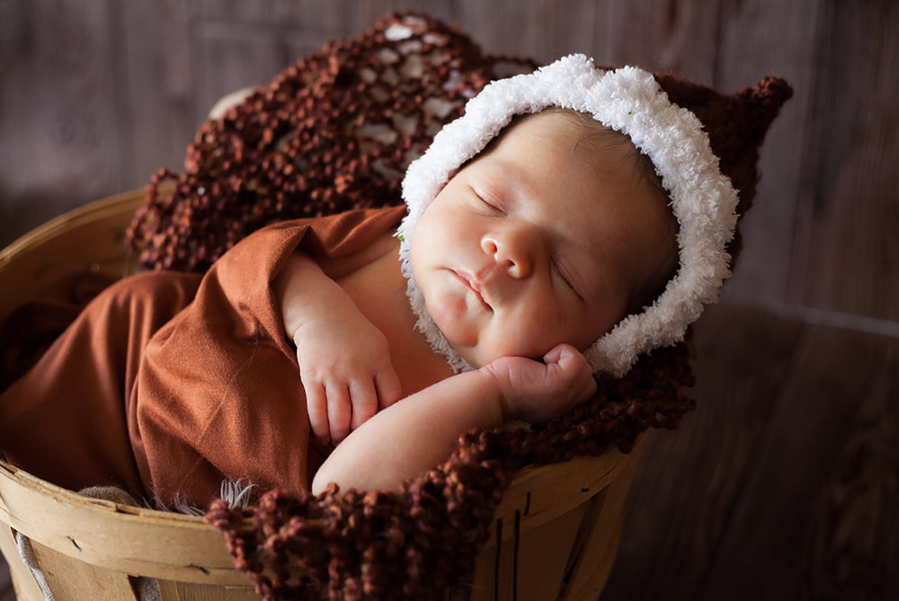 newborn baby sleeping in a basket and wearing fur trimmed bonnet