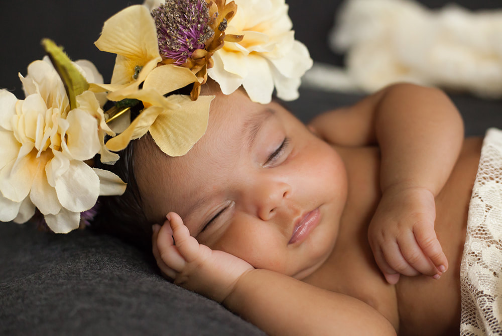 close up of sleeping baby girl with brown skin wearing a crown of flowers