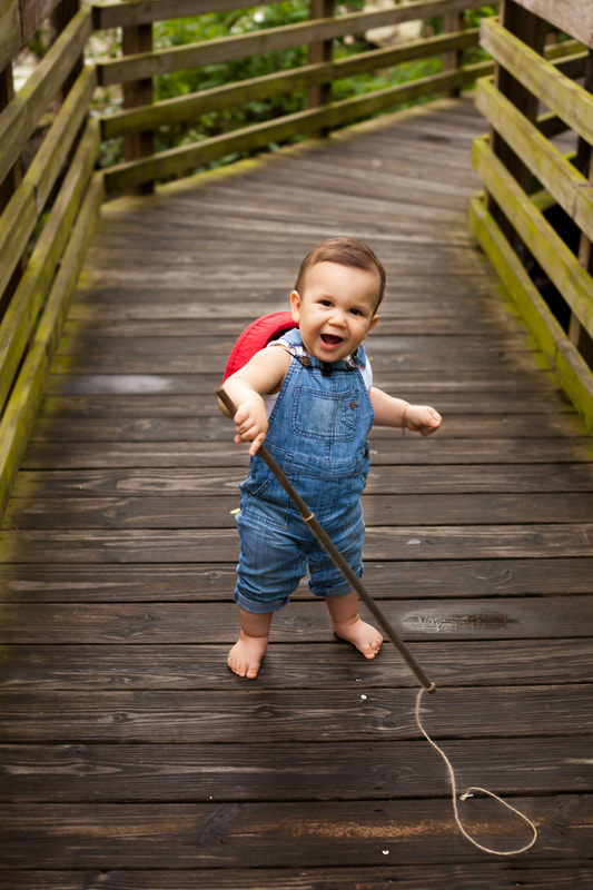 Baby boy in overalls standing on a fishing dock  with stick fishing pole