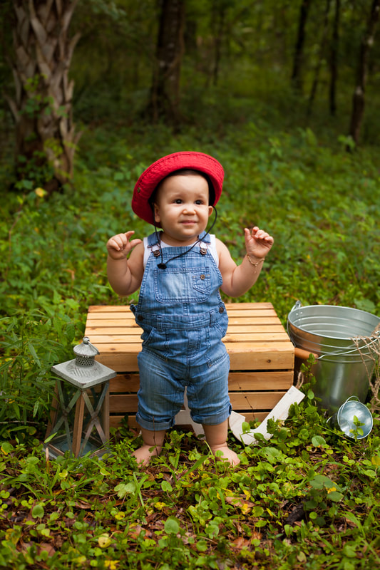 First Birthday boy standing in overalls and red fishing hat