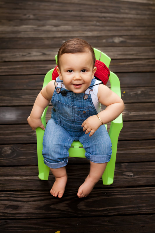 One year old boy in overalls sits in a bright green plastic chair on a dark wooden dock