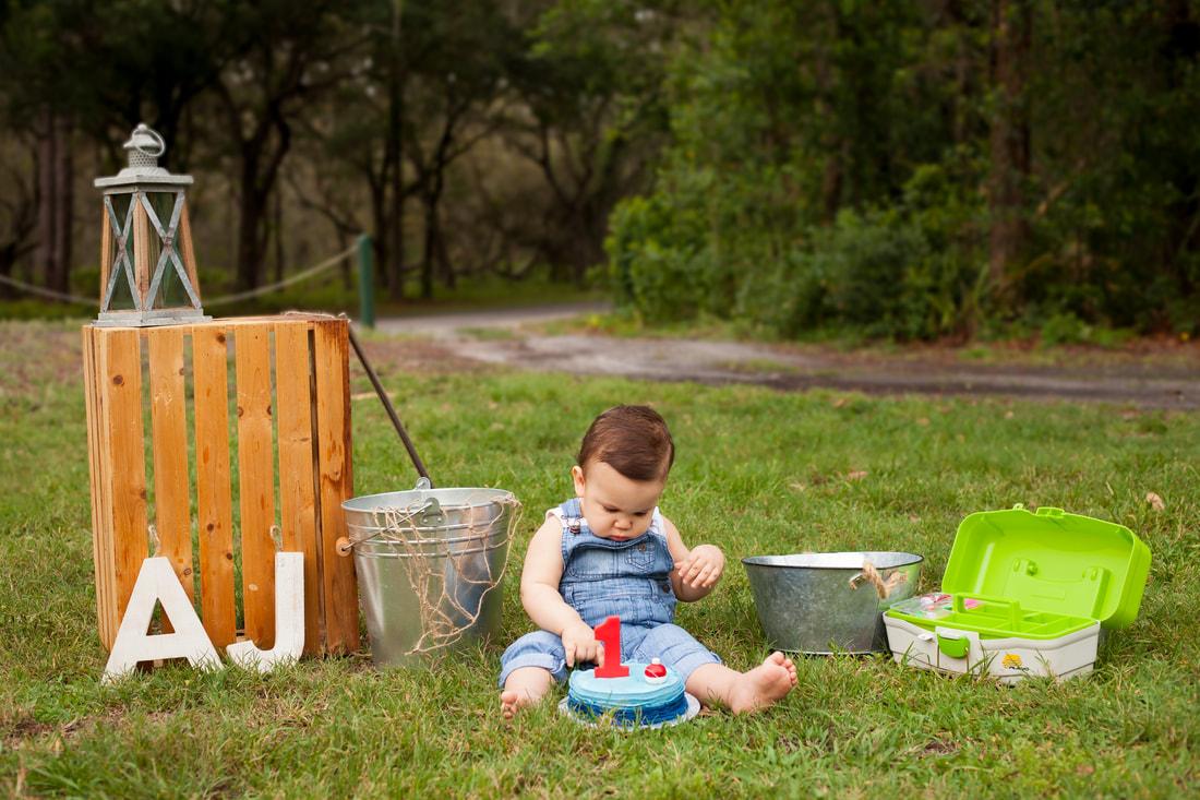 baby boy with his fishing themed first birthday cake in the grass outside