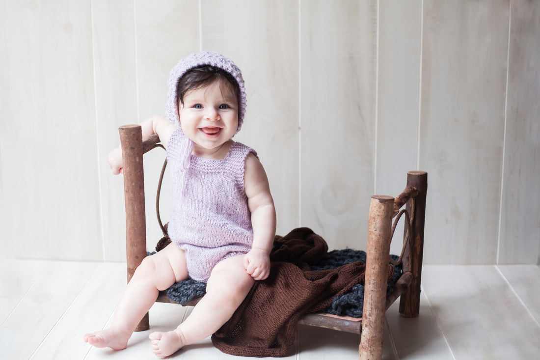 Six month old baby sits on bed in purple outfit and bonnet