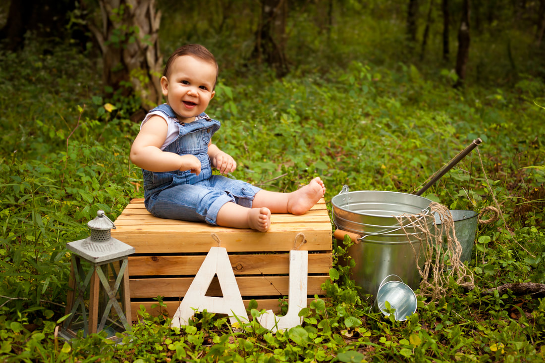 One Year Old boy in overalls sits on a crate in lush greenery surrounded by fishing props