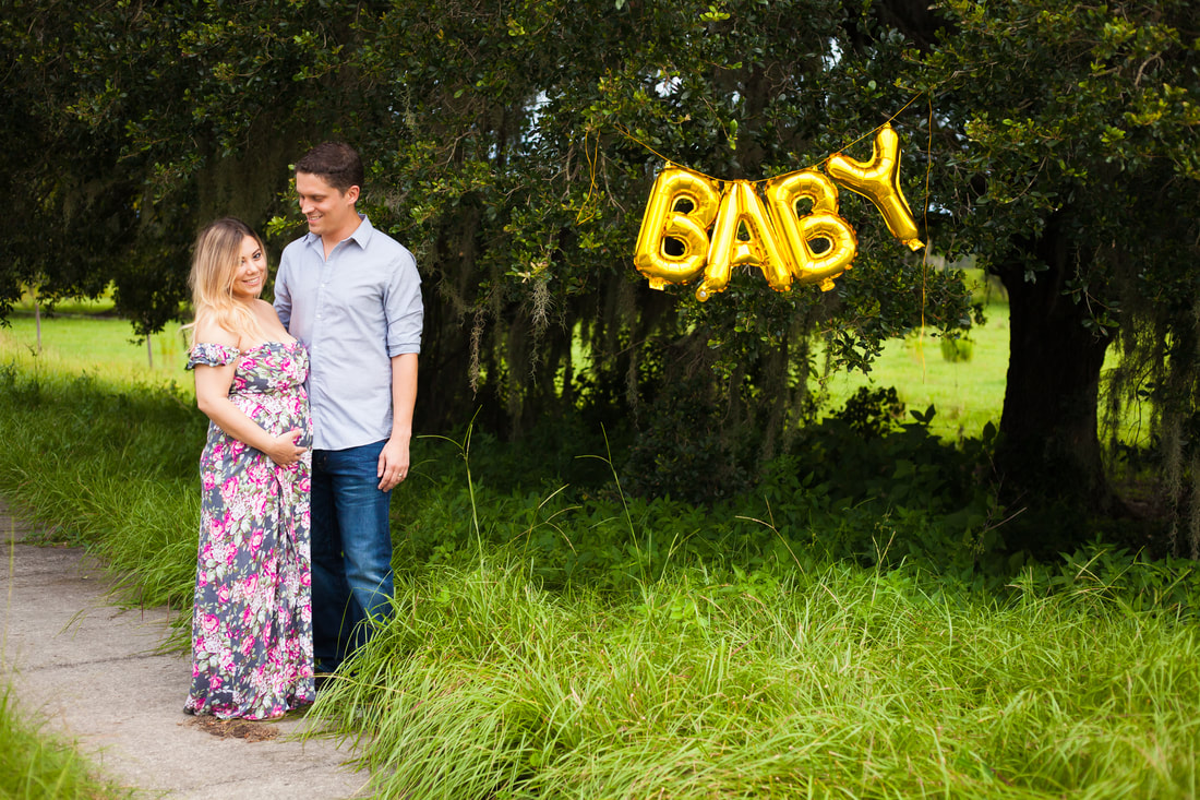 Maternity announcement photo of couple with balloon that reads 'baby' in Wesley Chapel Fl