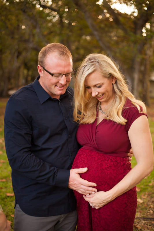 Maternity photo, mother-to-be and husband look down with their hands on the mother's belly