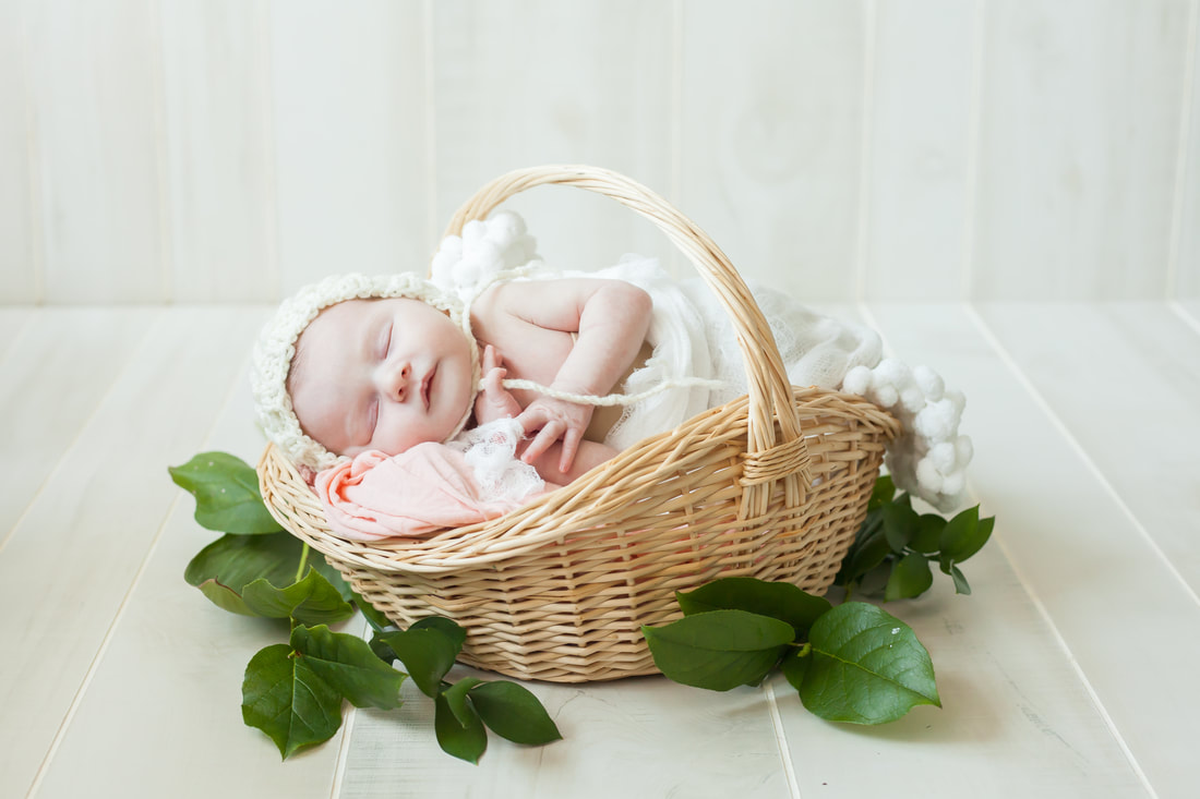 Newborn baby girl in a basket with a white bonnet on