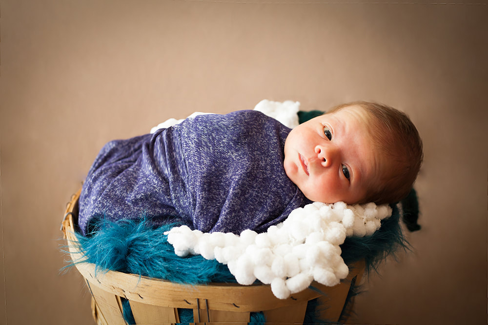 newborn baby swaddled and lying in a basket looks in to the camera