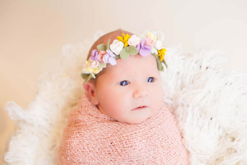 Wide awake newborn baby swaddled in pink with a flower headband on